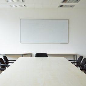 Leerer heller Konferenzraum mit Tafel und Flipchart
